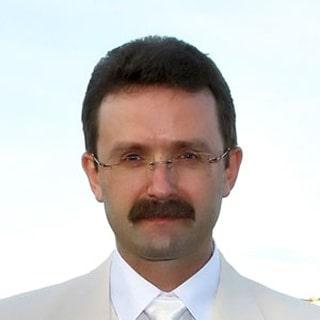 На фото: молодой человек в светлом костюме, смотрит прямо на вас, улыбается