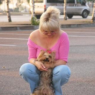 На фото: женщина в джинсах и розовой кофточке сидит на корточках в обнимку с йоркширским терьером с бантиком, блондинка с блондинкой, женщина смотрит вниз на терьера, терьер смотрит прямо на вас