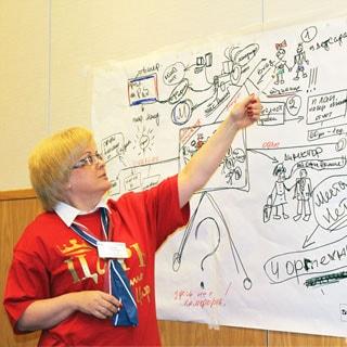На фото: женщина в красной футболке с надписью ЦАРЬ стоит с указкой у плаката со схемой и что-то объясняет, смотрит на схему
