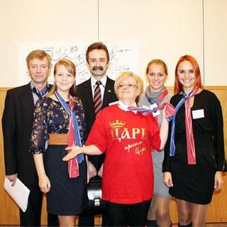На групповом фото: стоят четыре женщины и двое мужчин, офисный дресс-код, на переднем плане - женщина в красной футболке с надписью ЦАРЬ, голова приподнята, правая рука согнута в локте, ладонь обращена вверх, все смотрят на вас, женщины улыбаются