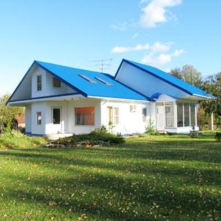 На фото: одноэтажный загородный дом белого цвета с голубой двускатной крышей, перед домом - лужайка