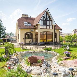На фото: одноэтажный загородный дом с высокой двускатной крышей, с мансардным этажом, перед домом - мощеная площадка, на переднем плане - газон с ландшафтным дизайном, прудом, клумбами, элементами уличного освещения