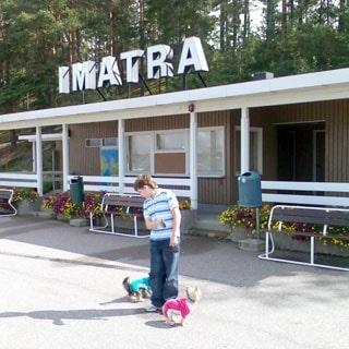 На фото: мальчик с двумя йоркширскими терьерами на прогулке, на заднем фоне одноэтажное строение с крышной рекламной установкой в виде отдельных букв, составляющих слово IMATRA