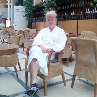 На фото: женщина в белом банном халате и шлепанцах, сидящая в кресле в холле, меблированным типовыми столиками и креслами