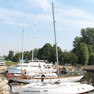 На фото: солнечный день, крейсерские яхты на воде у причальной стенки