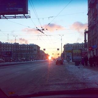 На фото: зимний вечер, закат солнца, перспектива городской полупустой улицы, вид через лобовое стекло автомобиля