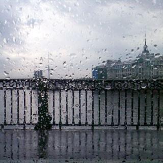 На фото: дождливый серый день, решетка Сампсониевского моста, за ней видна река Большая Невка, крейсер Аврора и Училищный Дом Петра Великого на Петровской набережной, вид через стекло в дождевых каплях
