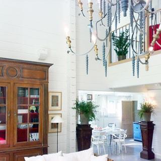 На фото: светлое внутреннее помещение, на переднем плане - шкаф, галерея второго этажа с перилами, кованая потолочная многорожковая люстра, на заднем плане - цветы на высоких подставках, обеденный стол со стульями