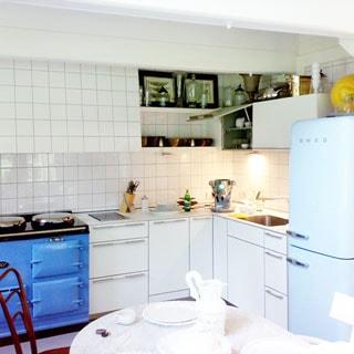 На фото: оборудованная и меблированная кухня-столовая, плита, мойка, холодильник, стенные навесные шкафы, напольные тумбы-столы, стены облицованы плиткой, на переднем плане - сервированный обеденный стол белого цвета со стульями