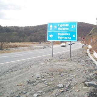 На фотографии: участок асфальтированной двухполосной трассы, проложенной у левой стороны крутого склона холма, развилка с ответвлением налево, дорожный указатель с обозначением поворота налево в сторону Войнежа и прямо в сторону Гурково, на трассе три легковые машины, на заднем плане слева - холмы, покрытые лесной растительностью, на небе - облачно