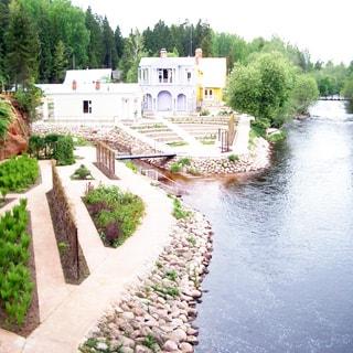 На летнем фото: небольшая река с пешеходным мостом на дальнем плане, на правом берегу реки - земельный участок с ландшафтным дизайном, клумбами, мощеными пешеходными дорожками, двумя одноэтажными домиками и одним двухэтажным, за ними слева и на дальнем плане - смешанный лес