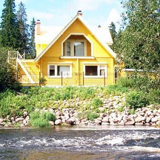 На летнем фото: берег реки, укрепленный валунами, на берегу - одноэтажный бревенчатый дом с мансардой и террасой, окна - стеклопакеты, участок перед домом огорожен металлическим забором, за домом на заднем плане - высокие ели