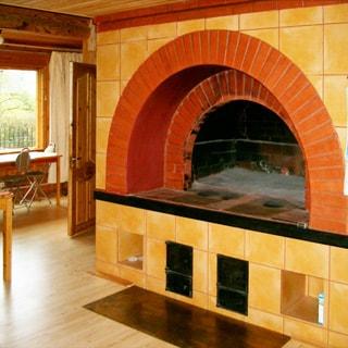 На фото: большая печь - камин от пола до потолка, облицованная кирпичом и плиткой, слева - соседняя комната с окном и письменным столом у окна, деревянная межкомнатная дверь, полы - ламинат, потолок обшит вагонкой