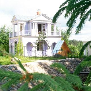 На летнем фото: двухэтажный загородный дом с огороженными перилами террасами на первом и втором этаже, скатная кровля, покрытая оцинкованной сталью, перед домом - колодец с крышей, пешеходные дорожки с перилами