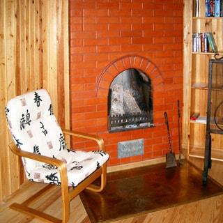 На фото: печь - камин, обложенная кирпичом, слева от печи - кресло, справа - книжный стеллаж с книгами, полы - дощатые, стены обшиты вагонкой