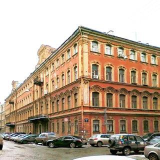 На фото: часть фасада 4-этажного здания старой постройки, вид с угла здания, проезжая часть прилегающих улиц с припаркованными автомобилями