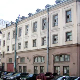 На фото: фасад 3-этажного здания старой постройки с высоким цокольным этажом (бывшие каретники), примыкающая дворовая территория с припаркованными автомобилями