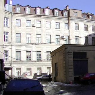 На фото: часть фасада 4-этажного здания с мансардным этажом, примыкающая дворовая территория, здание ТП, припаркованные автомобили