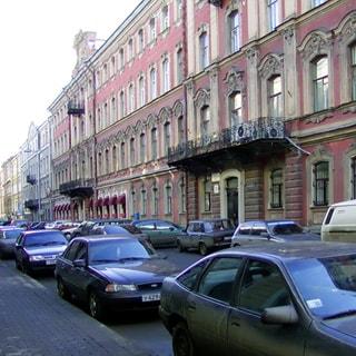 На фото: часть фасада 4-этажного здания старой постройки, с балконом, тротуар и проезжая часть прилегающей улицы с припаркованными автомобилями