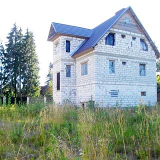 На фото: фасад трехуровнего блочного жилого дома, в окнах первого этажа - стеклопакеты, в окнах мансардного этажа - пленка, кровля - металлочерепица, участок - ровный, очищен, не обработан, огорожен забором, за участком - опушка леса