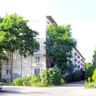 На летней фотографии: часть фасада пятиэтажного панельного многоквартирного жилого дома, балконы, вокруг дома - огороженный газон, деревья, кусты, тротуар и проезды - асфальтированы, припаркованы автомобили