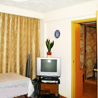 На фото: часть помещения жилой комнаты, окно закрыто шторами, у окна - обеденный стол, справ от окна в углу - тумба с телевизором, правее - открытая дверь в соседнюю комнату, стены окрашены