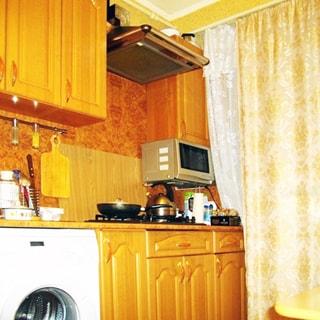 На фото: часть помещения кухни, окно закрыто шторой, от окна вдоль стены - кухонный гарнитур, столы-тумбы с общей столешницей, газовая плита, над ней - вытяжка, стиральная машина, навесные кухонные шкафы, микроволновая печь