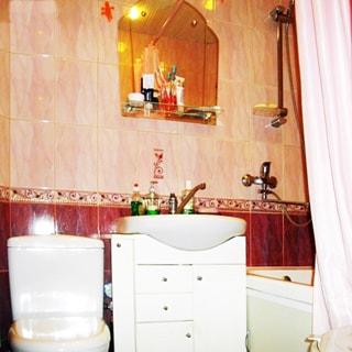 На фото: часть помещения совмещенного санузла, унитаз-компакт, керамическая раковина со смесителем - на тумбе с ящичками, над раковиной - зеркало с полочкой, справа - ванная со смесителем, стены облицованы керамической плиткой