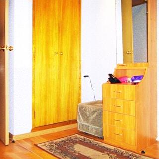 На фото: часть помещения прихожей, встроенный шкаф для одежды, пуф, небольшой комод со шкафчиком в полный рост с зеркальной дверцей, стены оклеены обоями, на полу - коврик