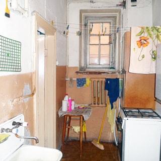 На фото: часть помещения кухни, одно окно, под окном батарея центрального отопления, справа у стены - четырехкомфорочная газовая плита с духовым шкафом, навесной кухонный шкаф, слева на стене - эмалированная мойка со смесителем, полы - линолеум, стены окрашены в пол-высоты