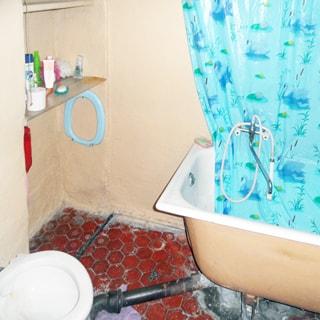 На фото: часть помещения совмещенного санузла, унитаз, ванная со смесителем, полы - плитка, стены окрашены