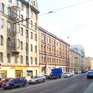 На фото: сторона улицы с расположенными на ней многоэтажными жилыми домами, дома разной этажности, в первых двух домах - цокольные этажи с витринными окнами и коммерческими помещениями, проезжая часть - четыре полосы, проезжающие и припаркованные автомобили
