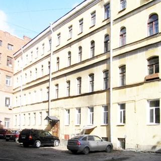 На фото: фасад четырехэтажного многоквартирного кирпичного дома со стороны двора, фасад оштукатурен, без балконов, одна парадная с козырьком, подвал с окнами, придомовая территория асфальтирована, припаркованы автомобили