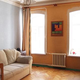 На фото: часть помещения жилой комнаты, два окна, между окон ниже уровня подоконника - радиатор центрального отопления, слева у стены - тумбочка, мягкий диван, полы - паркет, на потолке - люстра