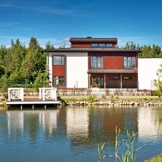На фото: современный двухэтажный загородный дом в стиле скандинавского конструктивизма, на переднем плане - пруд с оборудованным выходом к воде, на заднем плане за домом - лесной массив