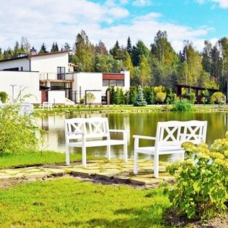 На фото: современный двухэтажный загородный дом в стиле скандинавского конструктивизма, хозяйственные пристройки и постройки, на переднем плане - пруд с оборудованным скамьями местом для отдыха, на заднем плане за домом - лесной массив