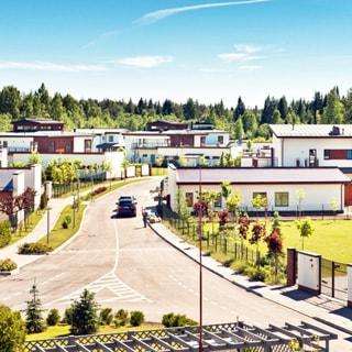 На фото: вид на коттеджный поселок, аккуратные загородные дома, асфальтированная проезжая часть, мощеные тротуары, газоны, декоративные
