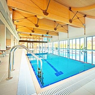 На фото: бассейн в помещении СПА центра, четыре дорожки, панорамные окна во всю стену, светло и просторно