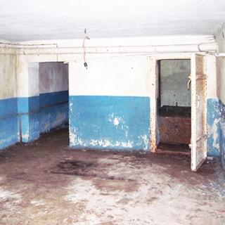 На фото: часть помещения, без окон, стены окрашены в половину высоты, полы - цементные, по стене проложена вентиляция, трубопроводы
