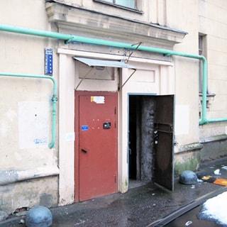 На фото: часть фасад здания и придомовой территории со стороны двора, вход в парадную, над входом в парадную - козырек, рядом соседняя дверь без козырька - вход в помещение, входная дверь - металлическая