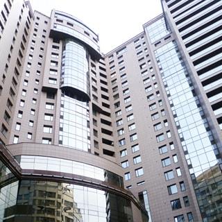 На фото: часть фасада современного многоэтажного дома, фасад облицован плиткой и остеклен, в нижних этажах центральной части фасада - сплошное панорамное остекление