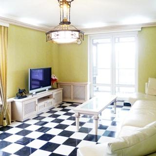 На фото: часть помещение жилой комнаты - гостиной, два окна, за одним - застекленная лоджия, справа вдоль всей стены - большой мягкий диван, перед ним - журнальный столик, напротив у противоположной стены - тумба, на ней - телевизионная панель, стены - окрашены, полы - плитка, на потолке - люстра