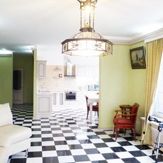 На фото: часть помещения жилой комнаты, справа - окно, слева от окна - мягкий стул с подлокотниками, слева напротив окна у стены - мягкий диван, прямо впереди - помещение кухни, стены - окрашены, полы - плитка, на потолке - люстра