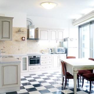 На фото: часть помещения кухни, справа падает свет от окна, встроенная кухонная мебель и кухонная техника, кухонная плита с духовым шкафом, над ней - вытяжка, в секции напротив окна - металлическая мойка со смесителем, фартук облицован керамической плиткой, справа - обеденный стол со стульями, полы - плитка