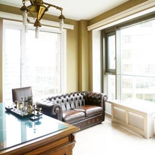 На фото: часть помещения жилой комнаты - кабинета, два окна, в углу - мягкий кожаный диван, слева от него - стул, еще левее - деревянный письменный стол, на столе - стекло, на стелке - письменные приборы, стены - окрашены, на потолке - люстра
