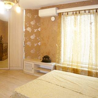 На фото: часть помещения жилой комнаты - спальни, одно окно, двуспальная кровать, слева от окна - небольшая тумба, над ней на стене - кондиционер, левее - встроенный шкаф-гардеробная, стены - оклеены обоями, полы - ламинат, на потолке - люстра