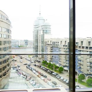 На фото: вид через окно на улицу, на улице - припаркованные автомобили, справа и слева - многоэтажные жилые дома, впереди на дальнем плане - выезд на набережную, видна поверхность водной глади и дома на противоположном берегу