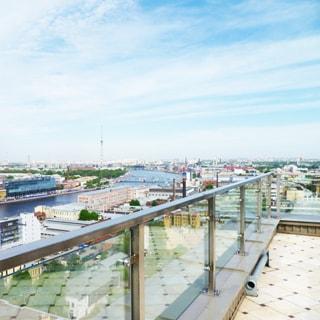На фото: панорамный вид на город с огороженной площадки на крыше дома, река, городские кварталы по обеим берегам реки, впереди вдалеке - телевизионная башня, ограждение площадки - металло-стеклянное, полы - плитка