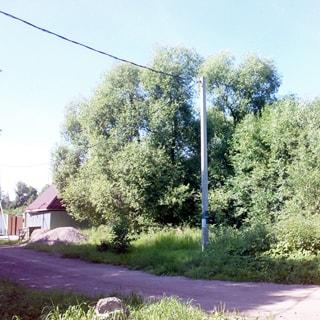На фото: вид с дороги на земельный участок, участок лесной, не разработан, на участке - лиственные деревья и кустарник, на обочине дороги со стороны участка - бетонный столб электропередачи, слева - соседний участок с домом