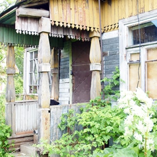 На фото: часть фасада дома, крыльцо с козырьком на резных деревянных колоннах, боковые деревянные перила, два окна с деревянными рамами, у дома - садовая растительность и посадки